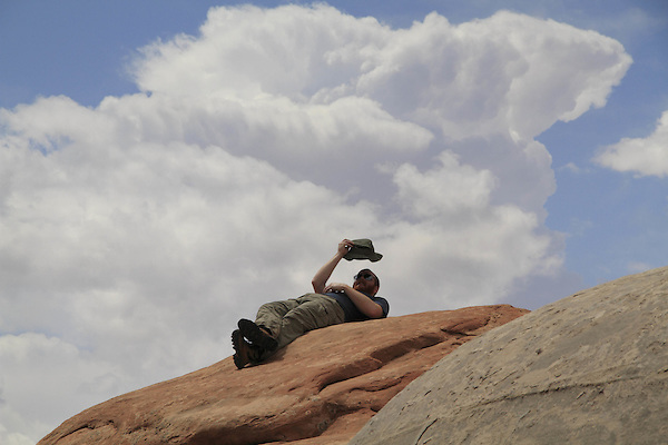 Man resting on slickrock under a thunderhead cloud in Arches National Park, Moab, Utah, USA. .  John offers private photo tours in Arches National Park and throughout Utah and Colorado. Year-round.