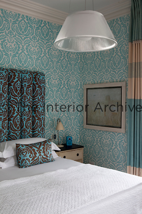 A bedroom decorated in shades blue with patterned wallpaper and a double bed with a upholstered headboard.