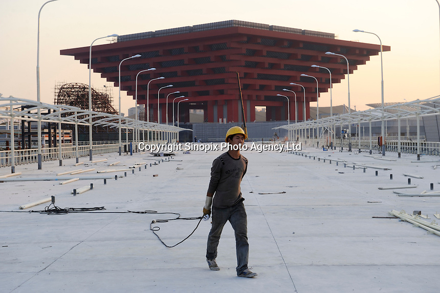 "Chinese workers at the construction site of China Pavilion of the World Expo 2010 in Shanghai, China. The China Pavilion is designed with the concept of ""Oriental Crown."" The traditional Chinese wooden structure element, Dougong brackets, is introduced. Its main colour is ""Gugong (Forbidden City) Red"" which represents the taste and spirit of Chinese culture. The permanent facilities including the World Expo Axis, Chinese Pavilion, Theme Pavilion, Performance Center and Expo Center of the World Expo 2010, will be completed by the end of this year..15 Oct 2009"