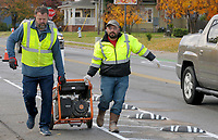 NWA Democrat-Gazette/DAVID GOTTSCHALK  Ryan Hale (left), founder of Lane Shift, and Mario Hernandez, with Boulder Construction, move a portable generator along a bike lane with newly installed Zebras, bike lane delineators and product from Spain, on Holcomb street in Springdale. Bike NWA is the pilot project owner working with Lane Shift the consultant that planned, designed and installed the bike lanes.