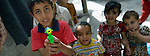 Boys with toy squirt guns play in the Al-Shalti refugee camp in Gaza. Residents of the Palestinian territory are still reeling from the death and destruction of the 2014 war with Israel, and the continuing siege of the seaside territory by the Israeli military.