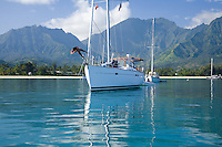 Asian local woman diving off the bow of a cruising sailboat in Hanalei Bay, Kauai
