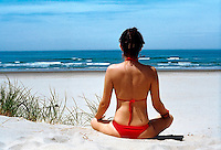 A woman meditates on an Oregon beach..MR