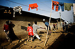 Tomas Hailemariam, 9, one of the first students at Fregenet School, jumps for a header while playing soccer with friends on his neighborhood street.  As a young boy, Tomas passed time in a similar way, kicking balled-up plastic bags around the same street in makeshift games of soccer. The family lives off the father's retirement pension, which is around $20 a month.