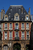 The ancient building at the entrance from rue de Bretagne of place des Vosges (XVII century) in Paris, with its three arcs, its red bricks, and its particular roof in slate. This is the Pavillon du Roi (the Pavillon of the King). Digitally Improved Photo.