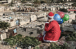 A picture taken on December 27, 2018 shows a Palestinian man Mohammed Abu Hajar, 28, dressed as Santa Claus with gifts bag on his shoulder looks to Nahr al-Bared refugee camp in Khan Younis in the southern Gaza Strip. Photo by Sanad Latifa