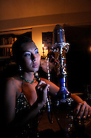 A woman smokes a hookah in an apartment in Waikiki, O'ahu.