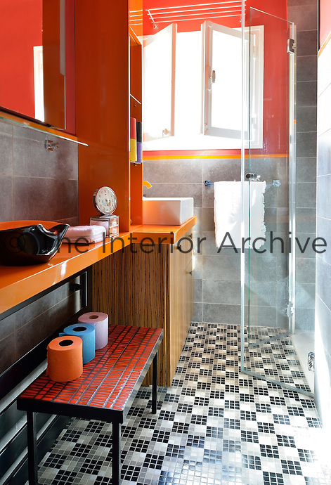 The floor of the bathroom features a geometric pattern of black and white mosaic tiles offset with grey ceramic wall tiles and an orange paint finish