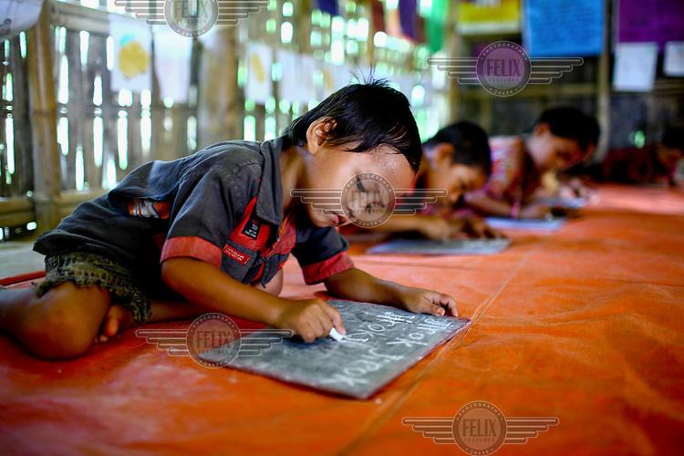 5 year old Juyel writes with chalk on a blackboard at Khumtai Ankur pre school in Kamini Para, Khargrachori.