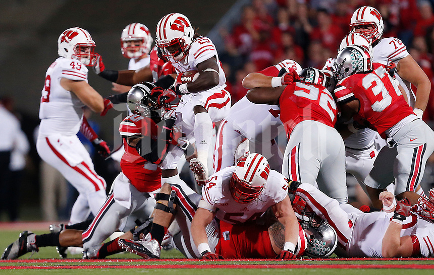 Wisconsin Badgers running back Melvin Gordon (25) tries to leap through a hole but gets stopped by Ohio State Buckeyes linebacker Ryan Shazier (10) in the second quarter of the NCAA football game at Ohio Stadium in Columbus, Saturday evening, September 28, 2013. The Ohio State Buckeyes defeated the Wisconsin Badgers 31 - 24. (Columbus Dispatch  / Eamon Queeney)
