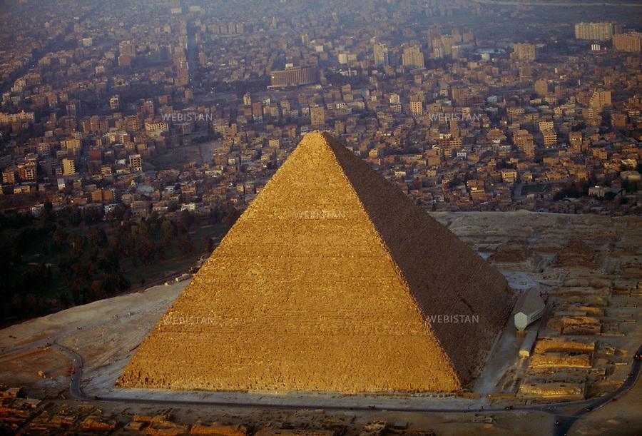 ..Egypt. Cairo. 1996. Aerial view of the Pyramid of Cheops: the Great Pyramid of Giza, the oldest and last remaining of the Seven Wonders of the World....Egypte. Le Caire. 1996. Vue aerienne de la pyramide de Kheops: la grande pyramide de Gizeh, consideree, depuis au moins 2 000 ans, comme la premiere des sept merveilles du monde et la seule ayant survecu.