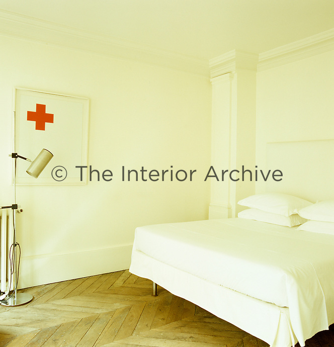 A painting by Jean-Pierre Reynaud adds a splash of red to the all-white bedroom