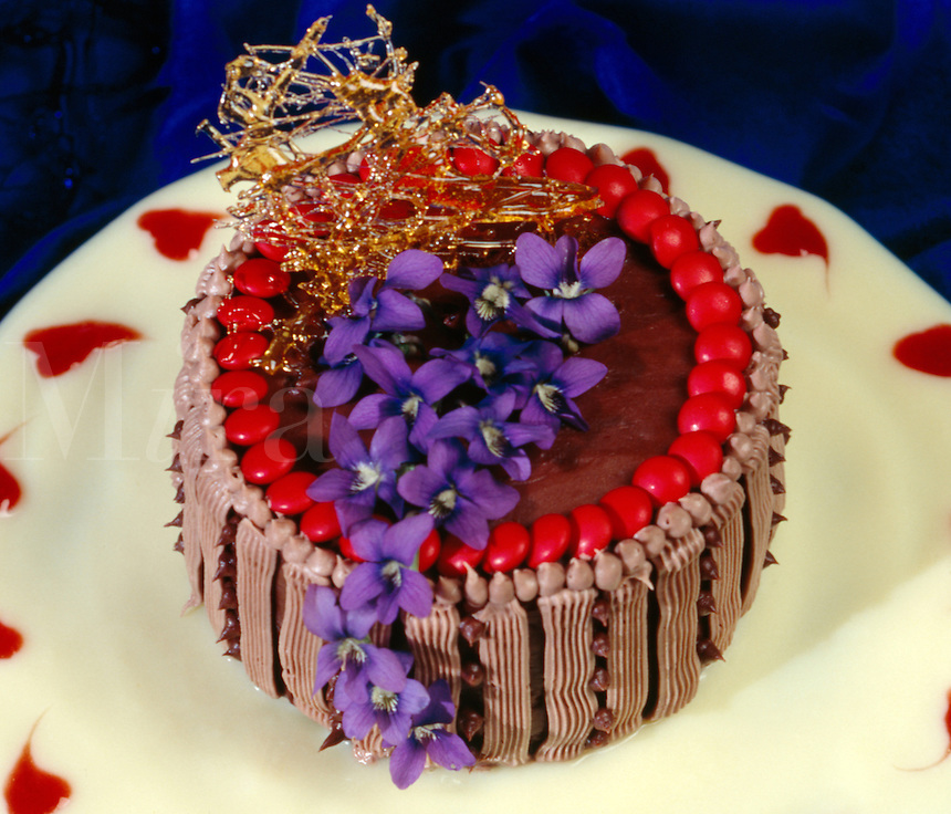 Fancy Chocolate Cake Served with Vanilla Sauce and Decorated with Fresh Purple Violets and Pulled Suga