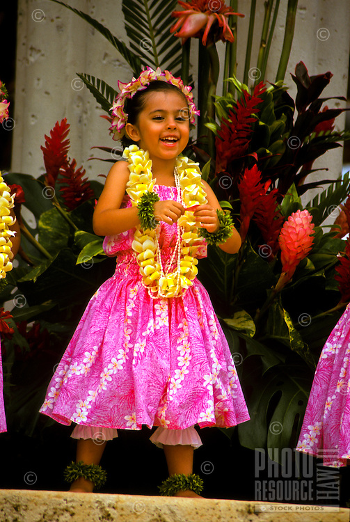 Young hula dancer wearing yellow plumeria lei, Lei Day celebration at Kapiolani Park Bandstand, Waikiki