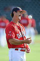 Pitching coach Paul Abbott (48) of the Greenville Drive tosses a ball while waiting for warmups before a game against the Asheville Tourists on Tuesday, July 1, 2014, at Fluor Field at the West End in Greenville, South Carolina. Asheville won, 5-2. (Tom Priddy/Four Seam Images)