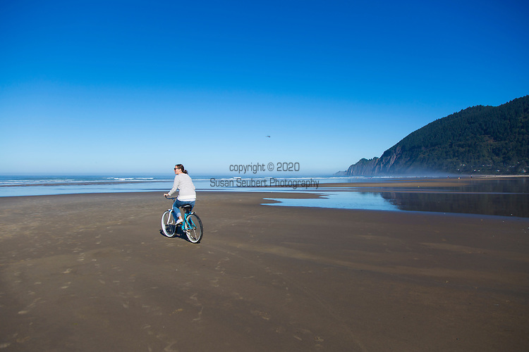 """Neahkahnie Beach in Manzanita, Oregon, a small beach town located in Tillamook County on the Northern Oregon coast.  Manzanita means """"little apple"""" in Spanish.  Neahkahnie Mountain is located at the north end of the 7 mile long beach. Friends riding bikes along the sand on the beach"""
