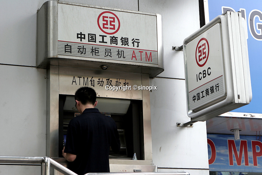 A man uses an ATM machine in an ICBC branch in Beijing, China..