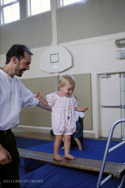Albany, CA  Father helping daughter two years old balance on plank at gymnastics program for preschool children  MR
