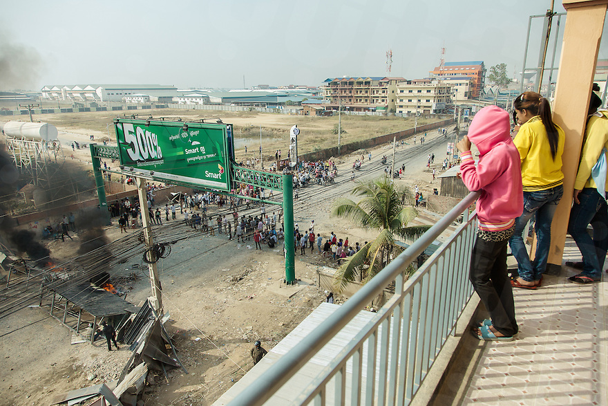 03 January, 2014 - Phnom Penh. Young factory workers watch the protesters from a balcony. © Thomas Cristofoletti / Ruom 2014