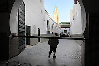 Man passing under the barrier beyond which non-muslims are not permitted, in the access corridor to the Mausoleum of Moulay Idriss I, running alongside a courtyard (through the horseshoe arches) and with the minaret above, Moulay Idriss, Meknes-Tafilalet, Northern Morocco. The mausoleum was rebuilt by Moulay Ismail, 1672-1727, in the 17th century and is the site of an important moussem or pilgrimage festival each summer. The town was founded by Moulay Idriss I, who arrived in 789 AD and ruled until 791, bringing Islam to Morocco and founding the Idrisid Dynasty. His body was moved to a tomb in the mausoleum. Picture by Manuel Cohen