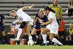 29 September 2011: Virginia's Shasta Fisher (12) is defended by Duke's Kaitlyn Kerr (left) and Duke's Mollie Pathman (right). The Duke University Blue Devils and the University of Virginia Cavaliers played to a 0-0 tie after overtime at Koskinen Stadium in Durham, North Carolina in an NCAA Division I Women's Soccer game.