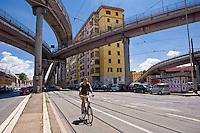 Un ciclista percorre un tratto di Via Prenestina sotto la Tangenziale Est della città