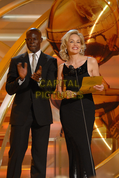 "DJIMON HOUNSOU & SHARON STONE.Present the award for Best Foreign Language Film.Telecast - 64th Annual Golden Globe Awards, Beverly Hills HIlton, Beverly Hills, California, USA..January 15th 2007. .globes stage microphone black suit jacket dress full length.CAP/AW.Please use accompanying story.Supplied by Capital Pictures.© HFPA"" and ""64th Golden Globe Awards"""