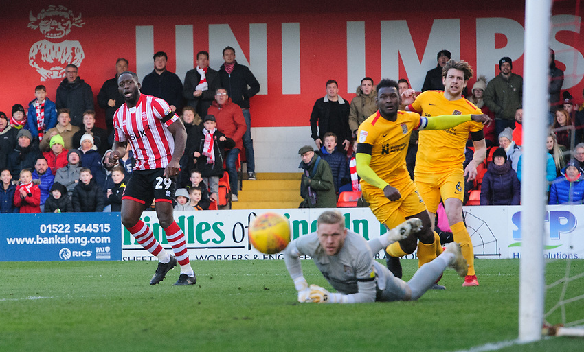 Lincoln City's John Akinde watches as his shot beats Northampton Town's David Cornell, but goes just wide<br /> <br /> Photographer Chris Vaughan/CameraSport<br /> <br /> The EFL Sky Bet League Two - Lincoln City v Northampton Town - Saturday 9th February 2019 - Sincil Bank - Lincoln<br /> <br /> World Copyright © 2019 CameraSport. All rights reserved. 43 Linden Ave. Countesthorpe. Leicester. England. LE8 5PG - Tel: +44 (0) 116 277 4147 - admin@camerasport.com - www.camerasport.com