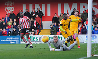 Lincoln City's John Akinde watches as his shot beats Northampton Town's David Cornell, but goes just wide<br /> <br /> Photographer Chris Vaughan/CameraSport<br /> <br /> The EFL Sky Bet League Two - Lincoln City v Northampton Town - Saturday 9th February 2019 - Sincil Bank - Lincoln<br /> <br /> World Copyright &copy; 2019 CameraSport. All rights reserved. 43 Linden Ave. Countesthorpe. Leicester. England. LE8 5PG - Tel: +44 (0) 116 277 4147 - admin@camerasport.com - www.camerasport.com