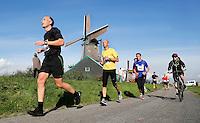 Zaanse Schans -  Deelnemer aan de Zaanse Schansloop. Op de achtergrond Molen de Kat
