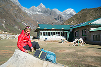 A woman sits outside a guesthouse using a solar panel while trekking in the Khumbu Valley, Nepal