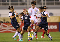 BOCA RATON, FL - DECEMBER 15, 2012: Carli Lloyd (10), Alex Morgan (13) and Shannon Boxx (7) of the USA WNT close down Wang Chen (16) China WNT during an international friendly match at FAU Stadium, in Boca Raton, Florida, on Saturday, December 15, 2012. USA won 4-1.