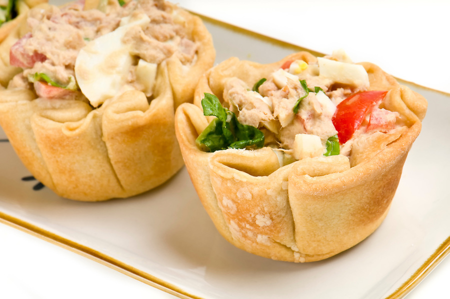 Homemade mini quiche of tuna and vegetables, in a tray.