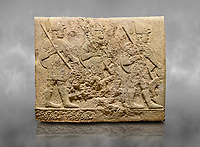 Hittite sculpted orthostats of Long Wall Limestone, Karkamıs, (Kargamıs), Carchemish (Karkemish), 900-700 BC. Anatolian Civilisations Museum, Ankara, Turkey<br /> <br /> Soldiers. Figure of three helmeted warriors. They have their shield in their back and their spear in their hand. The prisoners in their front are depicted as small. The lower part of the orthostat is decorated with wring / braiding motifs.<br /> <br /> On a grey art background.