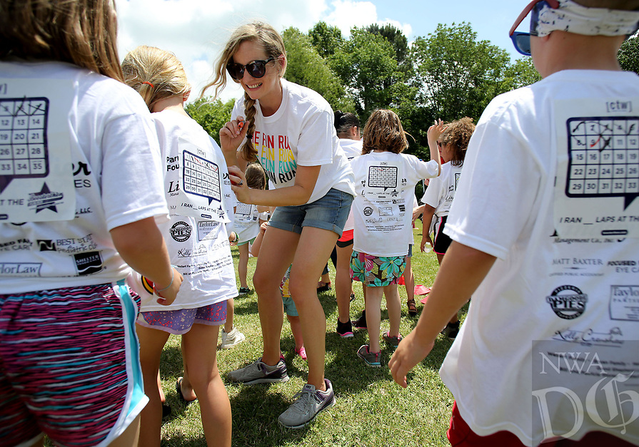 NWA Democrat-Gazette/DAVID GOTTSCHALK  Brooke Vickery, with the Parent Teacher Organization, marks off laps Thursday, May 18, 2017,  on the back of shirts of students during the Boosterthon Fun Run at Butterfield Trail Elementary School in Fayetteville. Kindergarten through fourth grade students participated in the interactive character program organized  by Boosterthon to raise funds for an indoor climbing wall and playground sports field at the school.