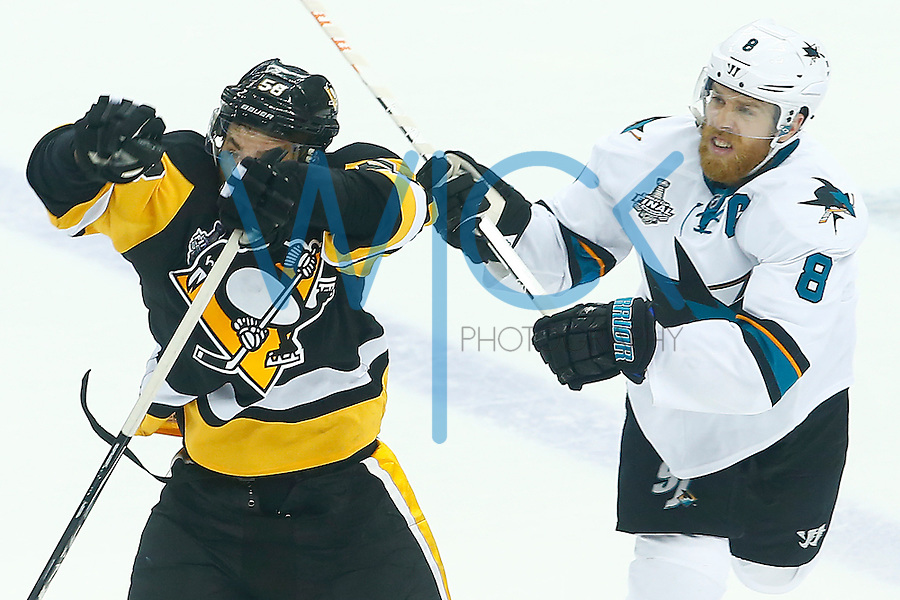 Kris Letang #58 of the Pittsburgh Penguins reaches for a puck in the air in front of Joe Pavelski #8 of the San Jose Sharks in the second period during game two of the Stanley Cup Final at Consol Energy Center in Pittsburgh, Pennslyvania on June 1, 2016. (Photo by Jared Wickerham / DKPS)