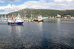 Boats at moorings and fishing boat and bridge at Tromso, Norway