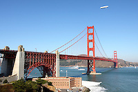 Escorted by a San Francisco fireboat a Zeppelin NT operated by Airship Ventures transits through the Golden Gate during its inaguaral voyage to San Francisco. The German manufactured airship differs from a blimp due to its rigid frame allowing for much larger aircraft.