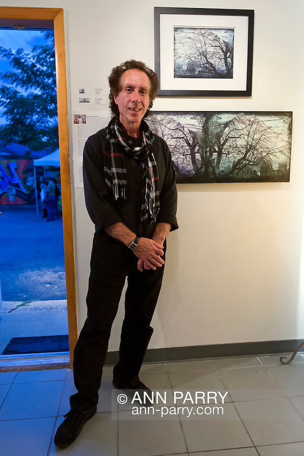 Massapequa, New York, USA. September 18, 2014. Artist MARK CHARLES ROONEY, of Hazleton, PA, stands next to his photographs Winter Trees, during Studio 5404 Art Space opening reception for art show Taking it to the Street,. The show featured new works by emerging and up-and-coming local and New York artists. Studio 5404 is on the South Shore of Long Island.