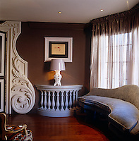 A curved sofa has been designed to fit the bay window of the drawing room, its shape echoing that of the bespoke console table and the ornate door frame