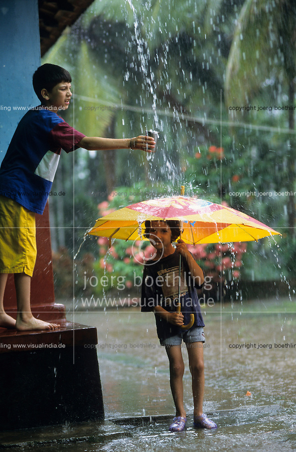 Asien Indien IND Karnataka, Kinder spielen mit Regenschirm im Monsun Regen / India Karnataka - children with umbrella play in Monsoon rain