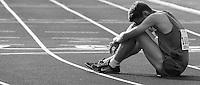 Ein Leichtathlet sitzt nach seinem Lauf erschöpft und enttäuscht auf der Bahn. Foto: Jan Kaefer / aif