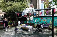 Nederland - Amsterdam - mei 2019.   Kunstenaar Gerti Bierenbroodspot is samen met kinderen van vluchtelingen en buurtkinderen begonnen aan een grote muurschildering in het centrum van Amsterdam. <br /> De schildering van 100 vierkante meter zal verschijnen op de muren van de Leidse Dwarstuin, een voorheen verwaarloosd stukje grond aan de Lange Leidsedwarsstraat. Het thema van de muurschildering is de natuur. De kinderen mogen zelf kiezen welk dier ze willen vereeuwigen en worden daarbij geholpen door Bierenbroodspot. De kinderen beschilderen de linkermuur. Gerti maakt een schildering van enkele etages hoog op de rechtermuur. Het project moet over enkele weken af zijn. De gemeente heeft opdracht gegeven voor de muurschildering om toeristen te laten zien dat het Leidsepleingebied een omgeving is waar mensen wonen.De kunstenaars in spé nemen even pauze.      Foto mag niet in negatieve / schadelijke context gepubliceerd worden.    Foto Berlinda van Dam / Hollandse Hoogte