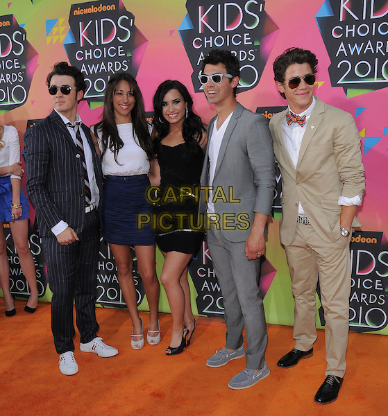 KEVIN JONAS , DANIELLE JONAS (nee DELEASA), DEMI LOVATO, JOE JONAS & NICK JONAS .at the 23rd Annual Nickelodeon Kids' Choice Awards 2010 held at Pauley Pavilion in Westwood, California, USA,.March 27th 2010                                                                                       .arrivals kids full length brothers wife husband couple family siblings sunglasses blue navy skirt white top t-shirt grey gray suit jacket jeans beige bow tie black dress strapless tie pinstripe red peep toe shoes trainers moccasins .CAP/RKE/DVS.©DVS/RockinExposures/Capital Pictures