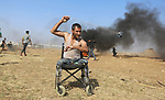 Saber al-Ashkar, 29, a Palestinian disabled protester hurls rocks during clashes tents protest where Palestinians demand the right to return to their homeland at the Israel-Gaza border, east of Gaza City, May 11, 2018. On 30 March 2018, Palestinians composed a series of protests was launched at the Gaza Strip, near the Gaza-Israel border. Called the Great March of Return, the protests demanded that Palestinian refugees and their descendants be allowed to return to the land they were displaced from in what is now Israel. They were also protesting the blockade of the Gaza Strip and the moving of the United States Embassy in Israel from Tel Aviv to Jerusalem. Photo by Ashraf Amra