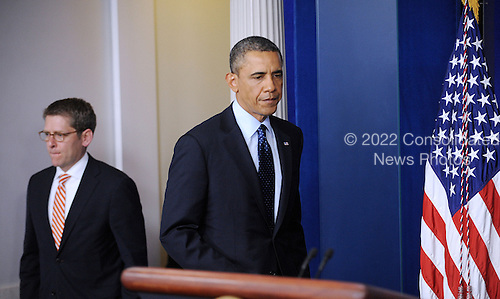 United States President Barack Obama makes his way to the podium of the Briefing Room of the White House as Press Secretary Jay Carney looks on before a statement to the press following explosions near the finish line of the Boston Marathon  April 15, 2013 in Washington, DC. .Credit: Olivier Douliery / Pool via CNP