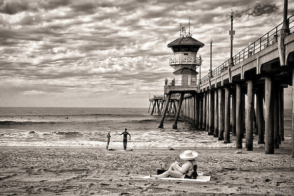 Woman sunbather and surfers on the beach near the pier.  Taken with infrared camera.