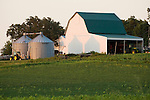 Farm with white barn, metal grain storage tanks, John Deere 4055 tractors