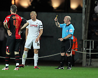 ATTENTION SPORTS PICTURE DESK<br /> Pictured: Garry Monk (L), captain for Swansea sees a yellow card by referee S A Hooper (R).<br /> Re: Npower Championship, Swansea City Football Club v Queens Park Rangers at the Liberty Stadium, Swansea, south Wales. Tuesday 19 October 2010