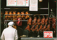 Man looks at roast duck and chicken hanging in window. Chinese menu. Asian American. Chinatown. San Francisco California USA Chinatown.
